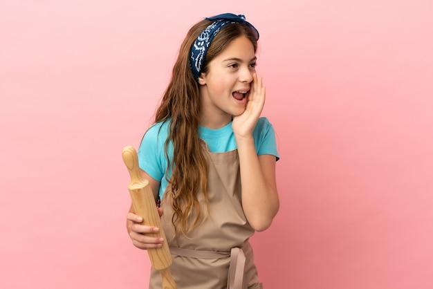 Kaukasisch meisje met een deegroller geïsoleerd op roze achtergrond schreeuwend met mond wijd open naar de zijkant