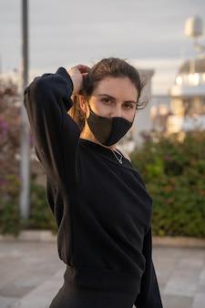Kaukasisch meisje met een masker dat naar de camera kijkt terwijl ze rolschaatsen draagt