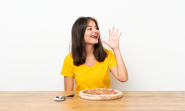 Kaukasisch meisje met een pizza die met wijd open mond schreeuwt