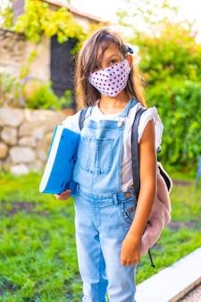 Kaukasisch meisje met gezichtsmasker klaar om terug naar school te gaan. nieuwe normaliteit, sociale afstand, coronavirus-pandemie, covid-19. jas, rugzak en een blauw blok voor aantekeningen in de hand
