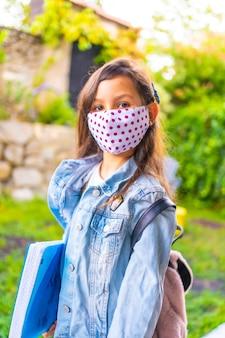 Kaukasisch meisje met gezichtsmasker klaar om terug naar school te gaan. nieuwe normaliteit, sociale afstand, coronavirus-pandemie, covid-19. jas, rugzak, masker met roze stippen en een blauw blok in de hand