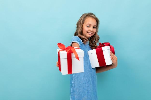 Kaukasisch meisje met golvend bruin haar in blauwe jurk, grote hoed houdt een dozen met geschenken en verheugt zich