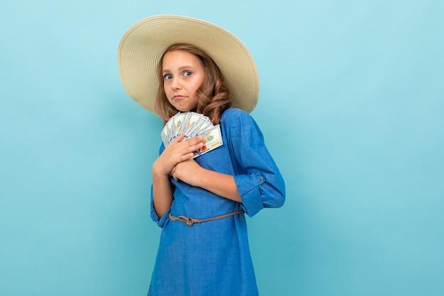 Kaukasisch meisje met golvend bruin haar in blauwe kleding, toont de grote hoed geld en verheugt zich geïsoleerd op blauwe achtergrond