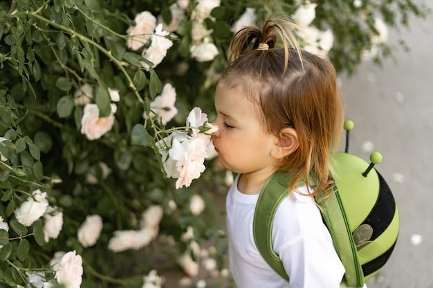 Kaukasisch meisje met groene rugzak die naar kleuterschool gaat. duurzaam onderwijs met liefde voor de natuur