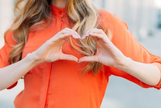 Kaukasisch meisje met handen maakt een hartvormig gebaar als symbool van liefde