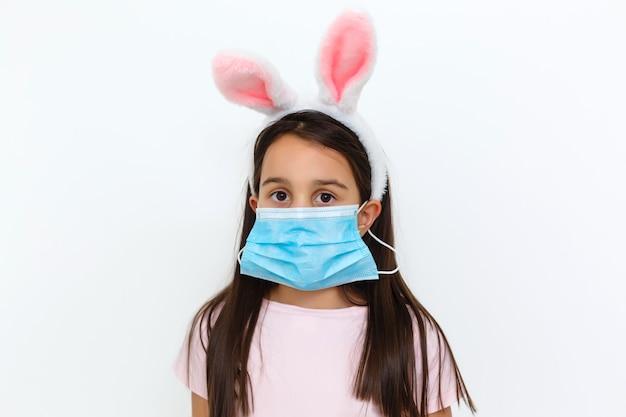 Kaukasisch meisje met konijnenoren en medisch masker op haar gezicht op een witte achtergrond. pasen-concept. coronavirus beschermd