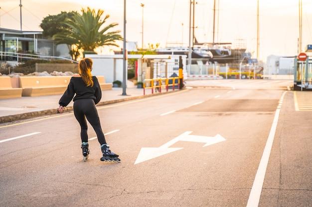 Kaukasisch meisje met masker dat op rolschaatsen schaatst bij zonsondergang
