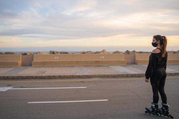 Kaukasisch meisje met masker schaatsen op rolschaatsen op de promenade bij een prachtige zonsondergang