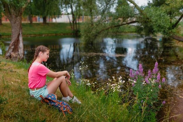 Kaukasisch meisje met sproeten en in een roze t-shirt zit op het gras. studente glimlacht en geniet van het mooie zomerweer.