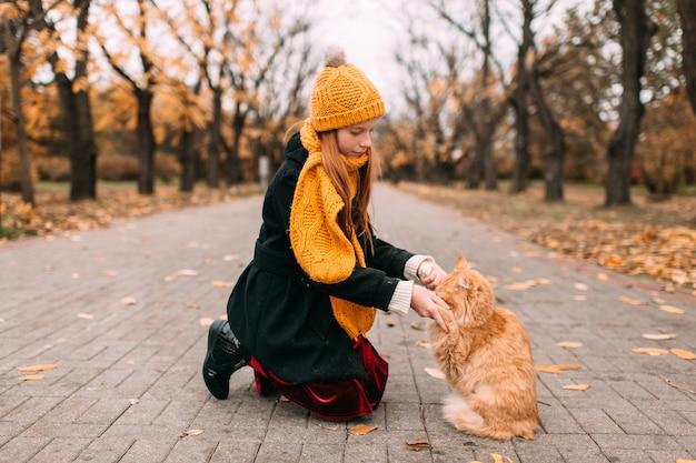 Kaukasisch meisje met sproeten gezicht haar mooie kitten spelen op de weg in de herfst park.