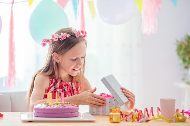 Kaukasisch meisje op verjaardag. feestelijke kleurrijke achtergrond met ballonnen. verjaardagsfeestje en wensen concept.