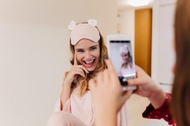 Kaukasisch meisje poseren met speelse glimlach voor zus. donkerbruine vrouw die met telefoon foto van haar vriend in roze eyemask neemt.