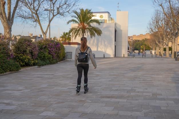 Kaukasisch meisje schaatsen op rolschaatsen op de promenade in palma de mallorca, spanje