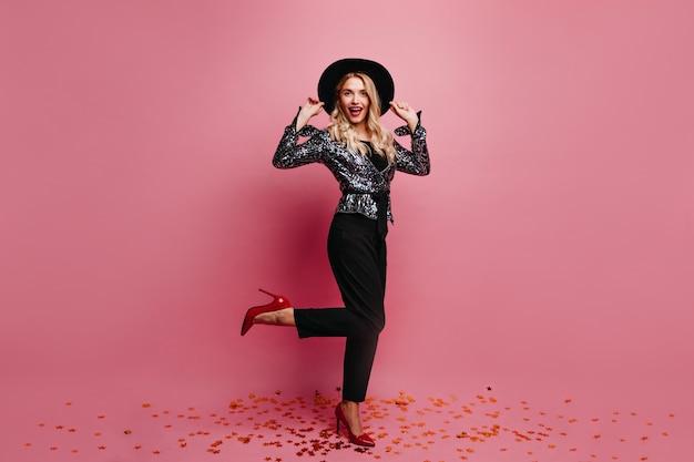 Kaukasisch meisje van gemiddelde lengte in zwarte broek die zich op één been bevindt. binnen schot van glimlachende blije vrouw in hoed.