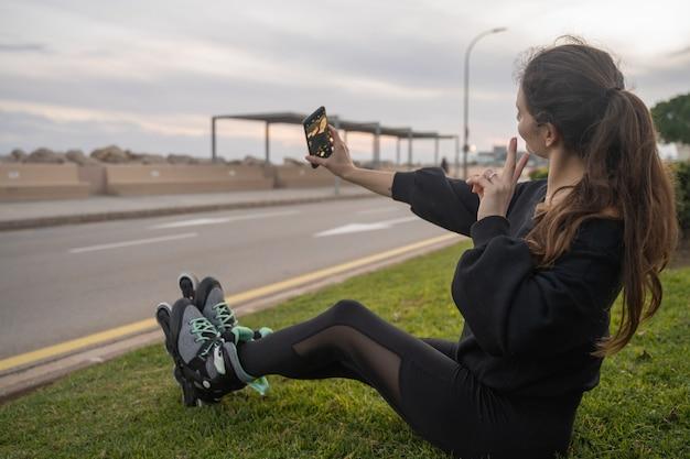 Kaukasisch meisje zittend op het gras met schaatsen bij het nemen van een selfie met een smartphone bij zonsondergang