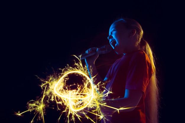 Kaukasisch meisjesportret dat op donkere studioachtergrond in neonlicht wordt geïsoleerd