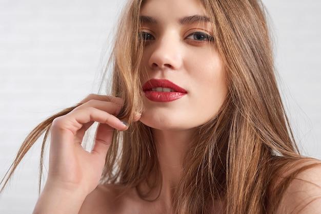 Kaukasisch model draagt oog make-up en rode lippenstift speels