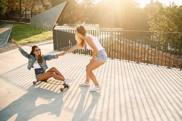 Kaukasisch mooi meisje zit op een longboard terwijl haar vriendin naar voren gaat en haar hand vasthoudt.