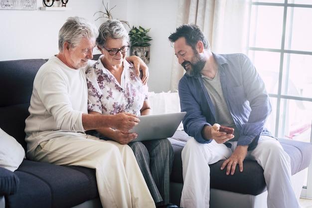 Kaukasisch ouder gezin thuis rijpt en mensen van middelbare leeftijd samen met behulp van technologische apparaten zoals laptop en mobiele telefoon die genieten van internetwebresultaten