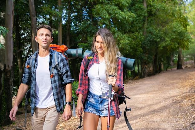 Kaukasisch paar dat in bos tijdens vakantie toert. gelukkige wandelaars die samen in het bos wandelen, genieten van de natuur, rugzakken dragen en praten. toerisme, avontuur en zomervakantie concept