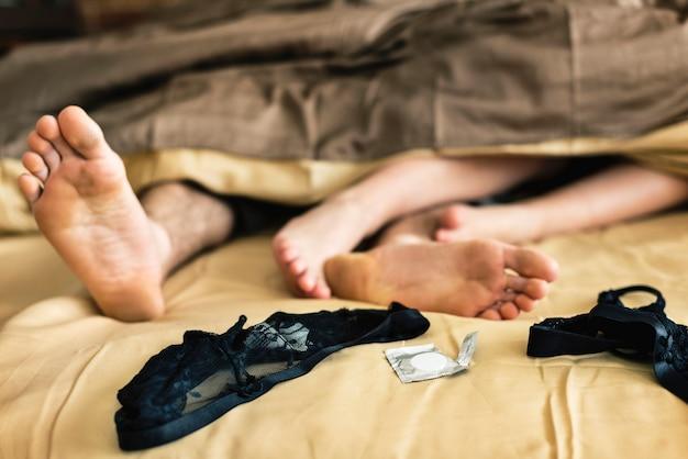 Kaukasisch paar dat op bed samen geslachtsconcept ligt