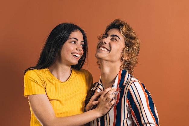 Kaukasisch paar dat samen lacht voor een bruine muur