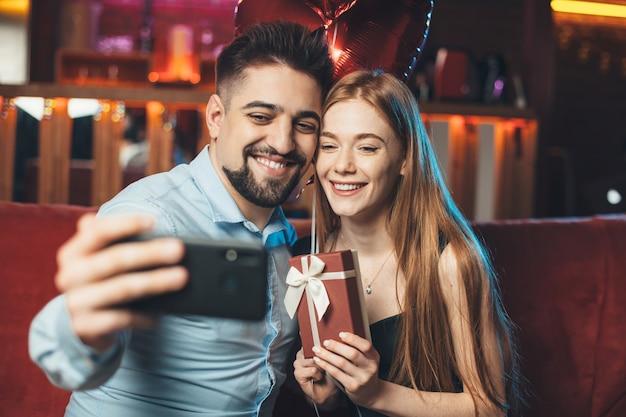 Kaukasisch paar dat valentijnsdag viert, houdt ballonnen vast en maakt een selfie met behulp van een telefoon