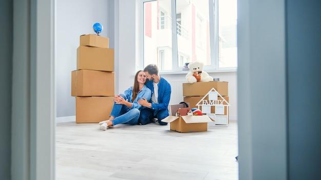 Kaukasisch paar dat zich in nieuw huis beweegt. jong modieus paar in zich het bewegen in puinhoop.