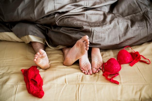 Kaukasisch paar die op het concept van het bed samen geslacht liggen