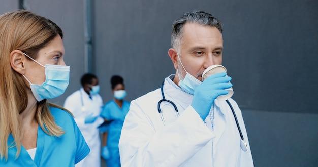 Kaukasisch paar, man en vrouw, artsencollega's in medische maskers lopen, praten en koffie drinken om te gaan. mannelijke en vrouwelijke artsen die werk bespreken en warme dranken nippen. arts en assistent.