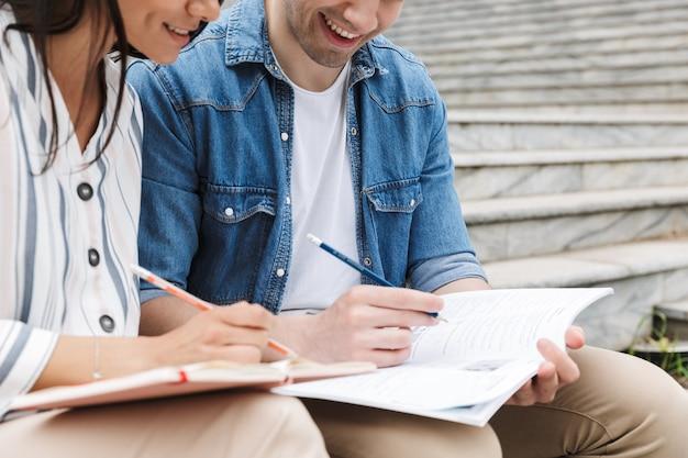 Kaukasisch paar man en vrouw in vrijetijdskleding praten en studeren terwijl ze op een bankje in de buurt van trappen buiten zitten