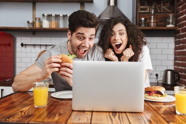 Kaukasisch paar man en vrouw kijken naar laptop op tafel terwijl ze thuis hamburger eten in de keuken