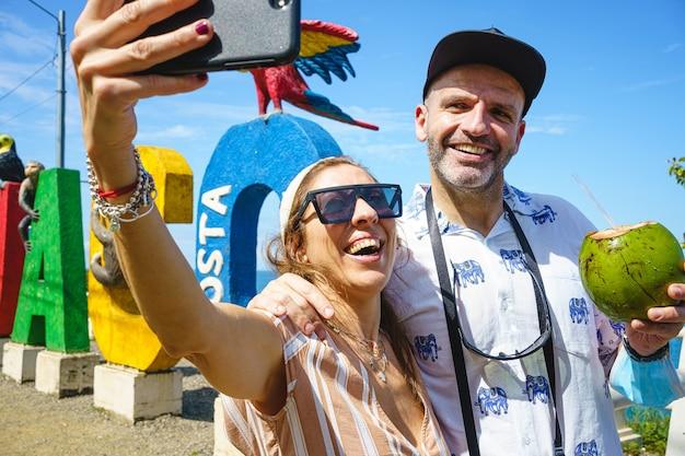 Kaukasisch paar van middelbare leeftijd dat een selfie maakt met een kokosnoot in hun hand naast costa rica-letters