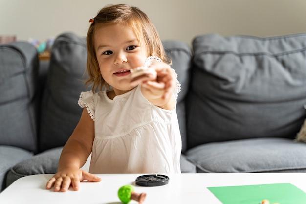 Kaukasisch peuter meisje spelen modellering spelen deeg thuis met moeder.