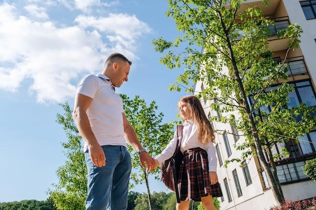Kaukasisch schoolmeisje met een rugzak en uniform houdt de hand van haar lachende vader vast