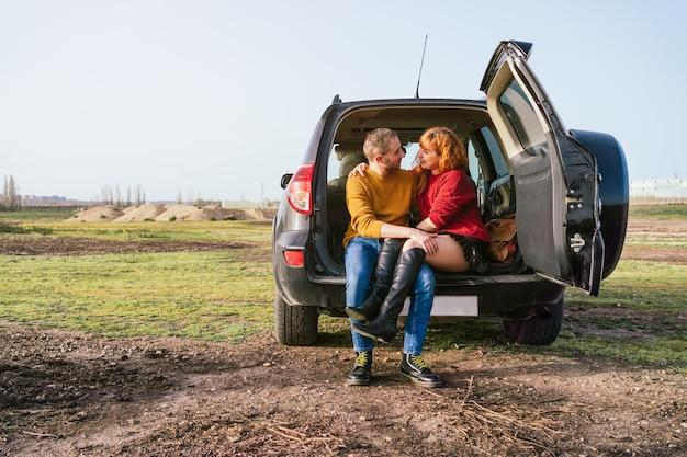 Kaukasisch stel zit in de kofferbak van een auto en kijkt elkaar aan met liefdesgezichten