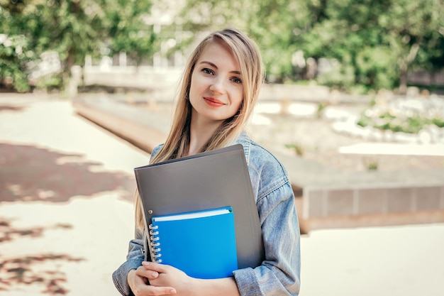 Kaukasisch studentenmeisje dat in het park loopt en notebookmappen in haar handen houdt onderwijs, concept van vreemde talen studeren