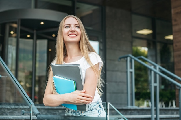 Kaukasisch studentenmeisje houdt mappen, notitieboekjes in handen en glimlacht op de achtergrond van het universiteitsgebouw en kijkt weg. ruimte kopiëren