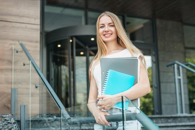 Kaukasisch studentenmeisje houdt mappen, notitieboekjes in handen en glimlacht op de achtergrond van het universiteitsgebouw. ruimte kopiëren