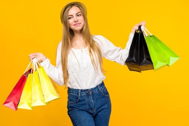 Kaukasisch tienermeisje op geel. stijlvolle jonge vrouw met boodschappentassen in handen -