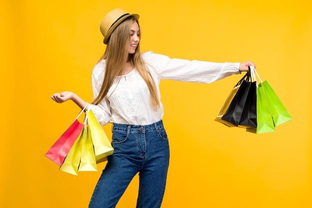Kaukasisch tienermeisje op gele achtergrond. stijlvolle jonge vrouw met boodschappentassen in handen - afbeelding