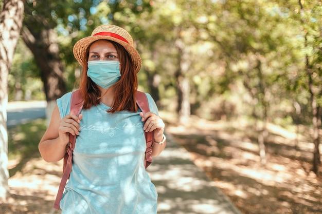 Kaukasisch toeristenmeisje in een zomerstrohoed en t-shirt met een rugzak en een beschermend masker op een openbare plaats. t