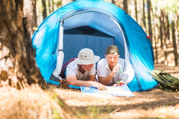 Kaukasisch volwassen koppel ging in een tent liggen terwijl ze op een kaart de volgende stap van hun reis kiezen en plannen - vrijetijdsbesteding in de natuurlevensstijl voor alternatieve gepensioneerden