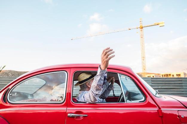 Kaukasisch volwassen stel reizen en rijden op een rode vintage auto