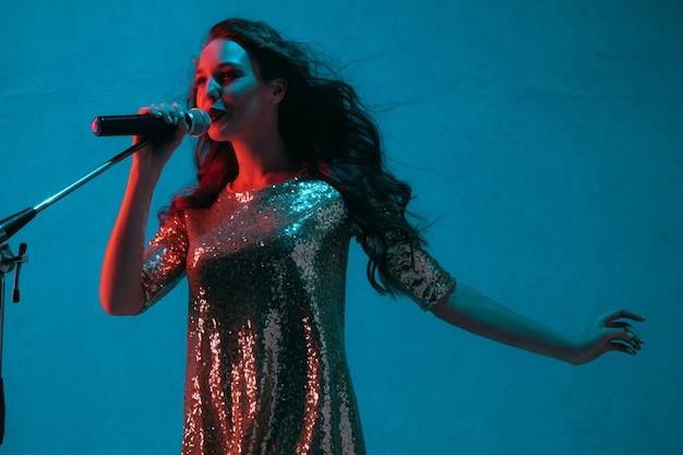 Kaukasisch zangeres portret geïsoleerd op blauwe studio achtergrond in neonlicht. mooi vrouwelijk model in lichte kleding met microfoon. concept van menselijke emoties, gezichtsuitdrukking, advertentie, muziek, kunst.