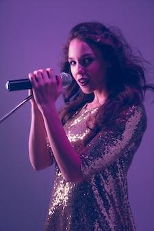 Kaukasisch zangeres portret geïsoleerd op paarse studio in neonlicht