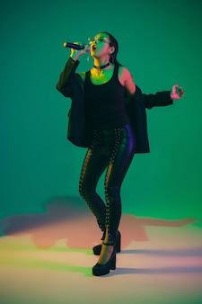 Kaukasisch zangeresportret dat op groene studiomuur wordt geïsoleerd
