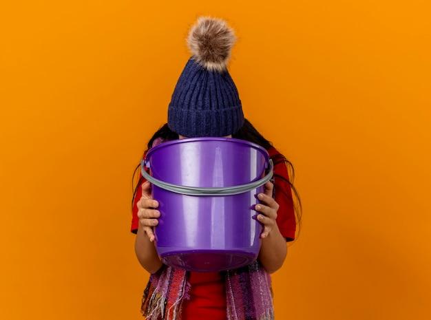 Kaukasisch ziek meisje dragen winter hoed en sjaal braken in plastic emmer geïsoleerd op een oranje achtergrond met kopie ruimte