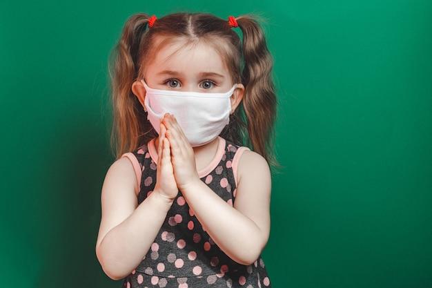 Kaukasisch ziek meisje in medisch masker bidt tijdens coronavirus-epidemie op groene achtergrond close-up 2021