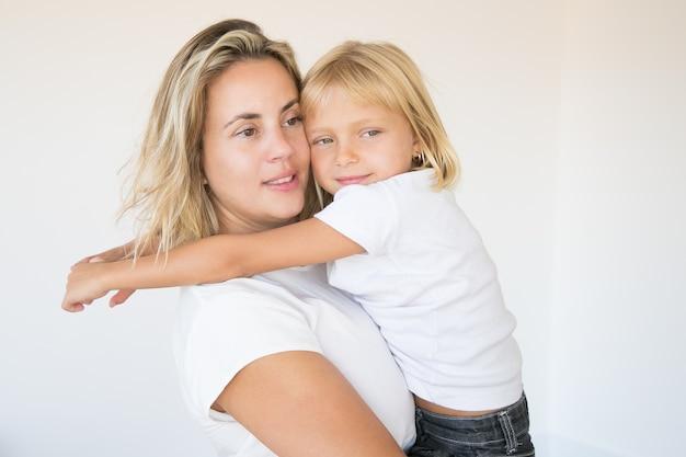 Kaukasische aantrekkelijke moeder die dochter houdt en weg kijkt
